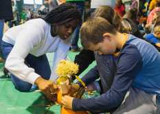 Ayanna Jefferson '22 helps a Lower School student decorate a pumpkin.