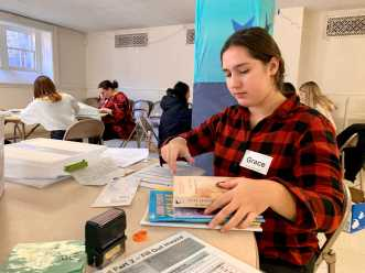 Grace Papas '23 gathers books at the Invoicing table. Photo by Edan Zinn '23.