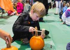 A Lower School student uses cranberries to decorate his pumpkin.