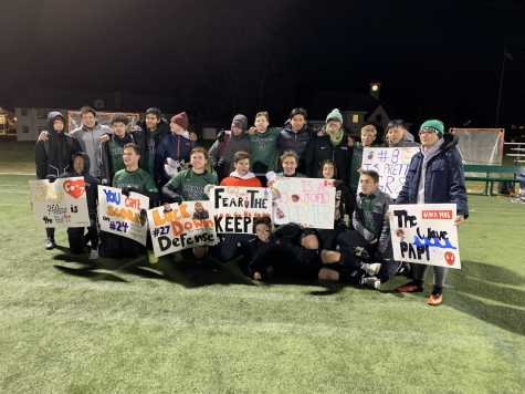 The team celebrates after its victory against Gann Academy, while also showing off fan signs. Photo by Dr. Nathalie Boileau