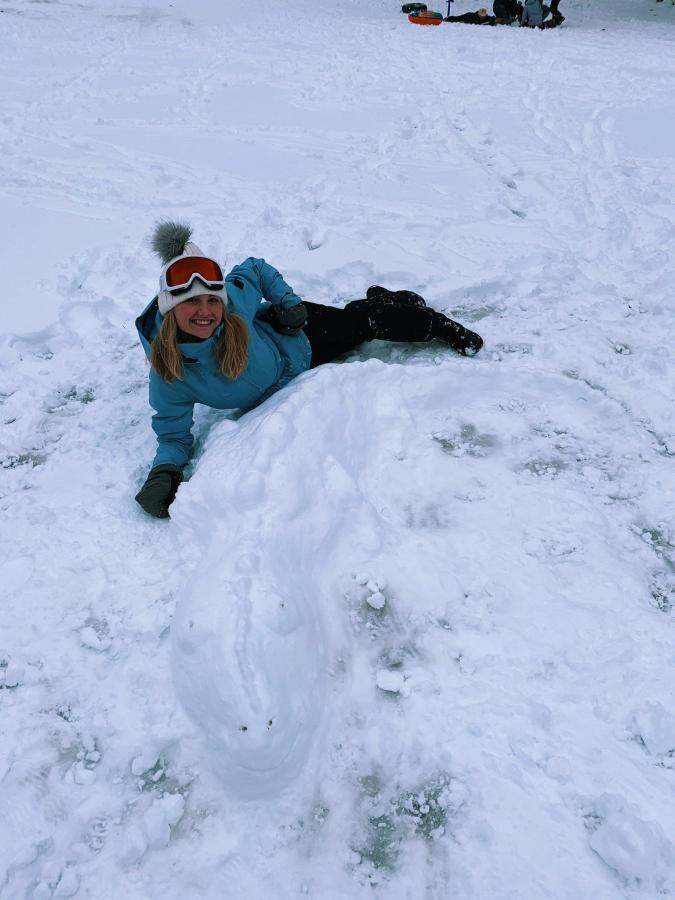 The contest's winner, Eleanor Reyelt '23, posed in the snow with her handmade gator snow sculpture.