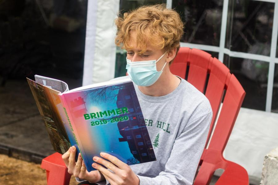 Brian Gamble '23 reads the 2019-2020 yearbook. Photo illustration by Edan Zinn '23.