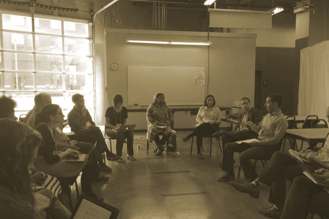 A group of people sitting in chairs arranged in a circle in a large room with a glass-paneled wall in the background.