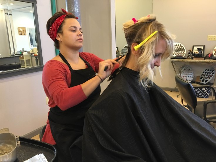Tiaa Ferrebee, hair dresser, concentrates on her highlight application for her client Christy Williams at The Beauty Bar on Sept. 27, in Morgantown, W. Va. This was Tiaa's first client of the day. Photo by Blaithe Tarley.