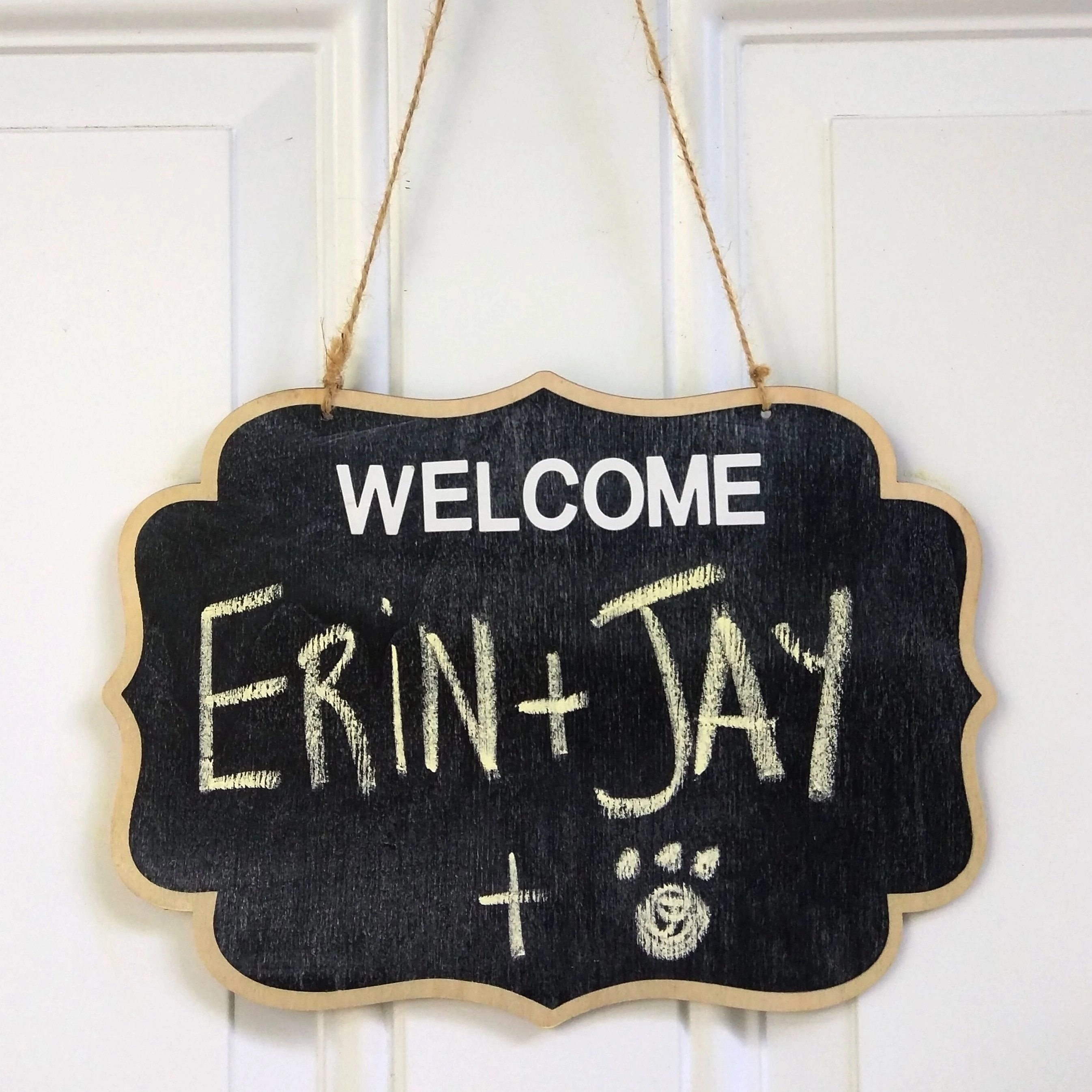 """A sign hangs to welcome us to our new Airbnb home: """"WELCOME! Erin + Jay + Puppy"""""""