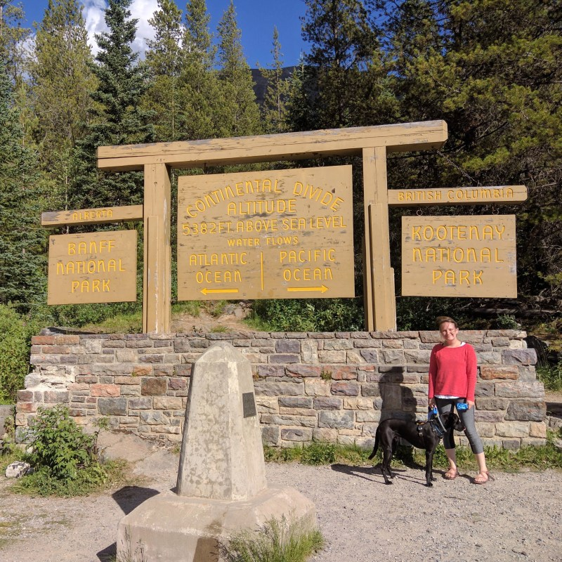 Erin and Odin at Banff National Park at the continental divide sign