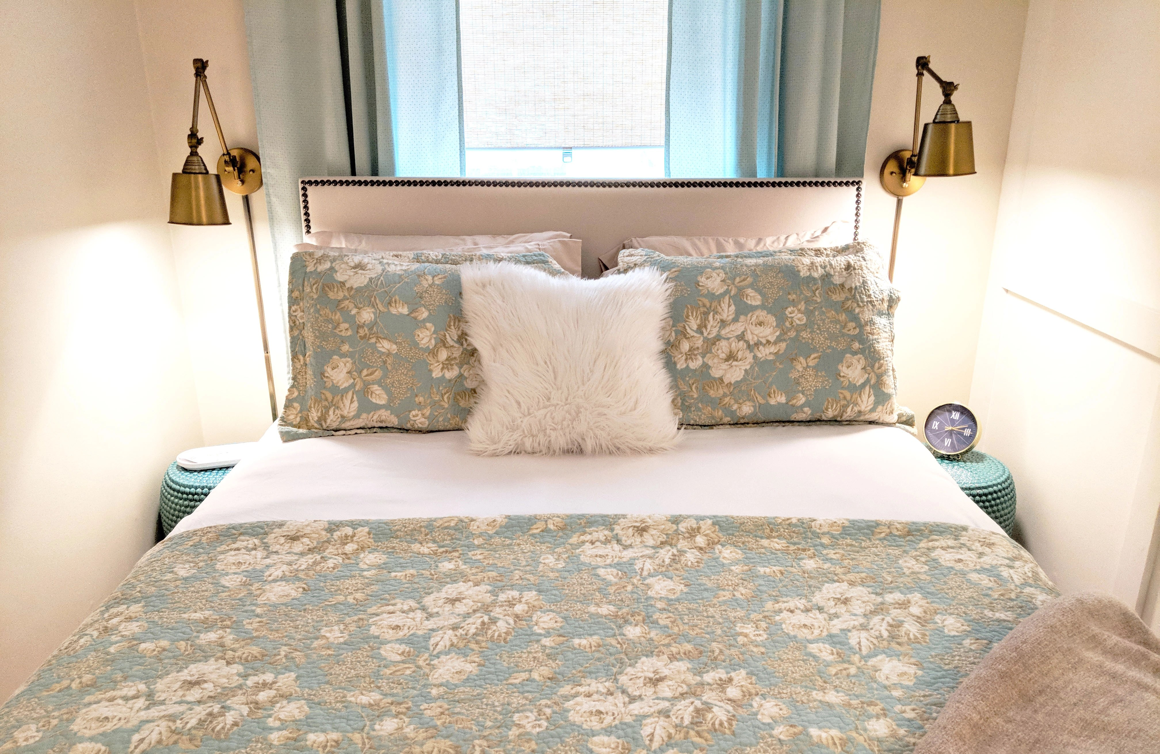 bed with teal quilt and many pillows