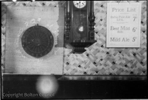 Dartboard and price list on the wall of a Bolton pub, 1930s.