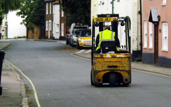A forklift truck on a quiet street.