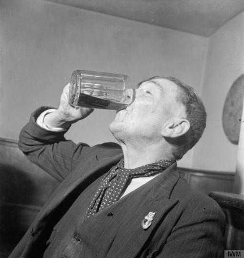A man downs dark mild from a ten-sided pint glass.