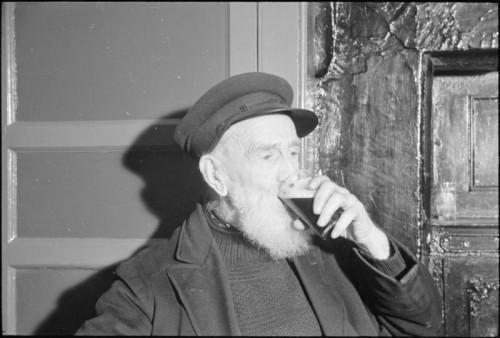 An elderly bearded man drinking beer.