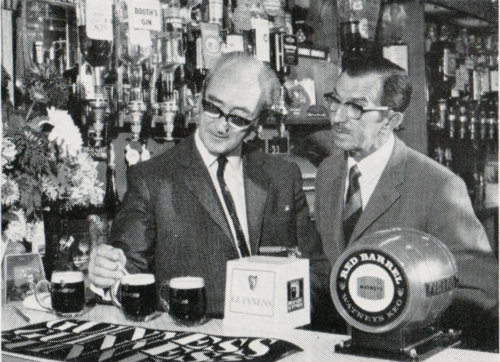 1970s photograph of two men in horn-rimmed glasses inspecting beer.