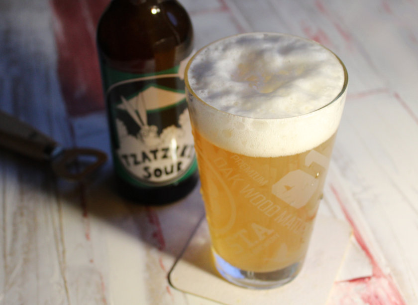 Tzatziki Sour: bottle next to glass full of beer.