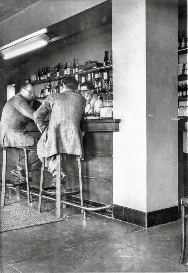 Two men in suits sitting at a bar; bespectacled landlord serving.