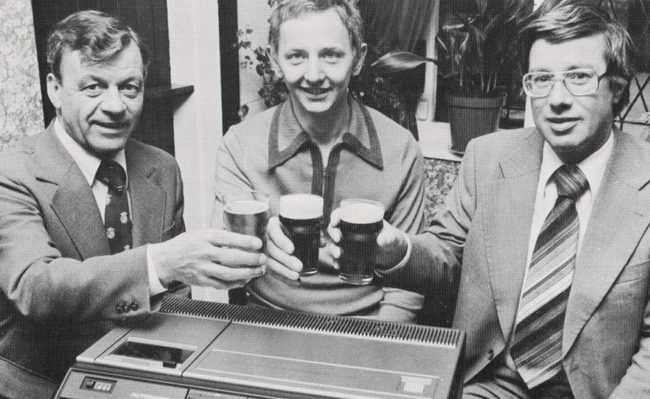 Three men raising pints over a video recorder.