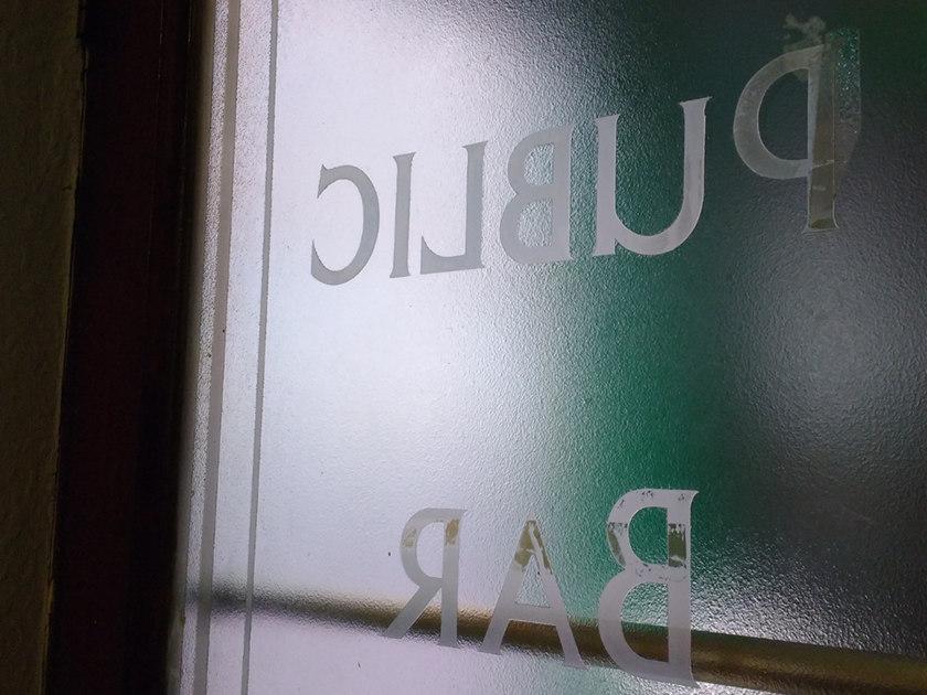 """""""Public Bar"""" -- sign on pub door."""