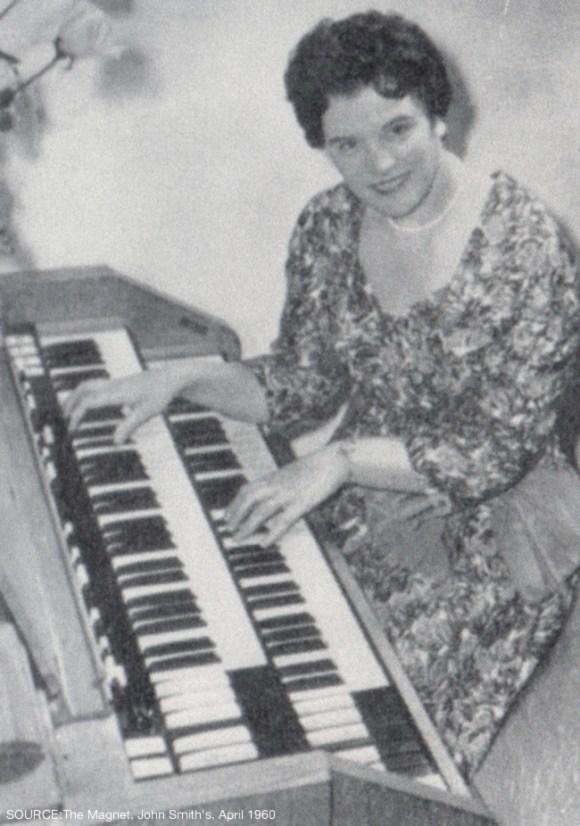 A woman plays the Hammond organ.
