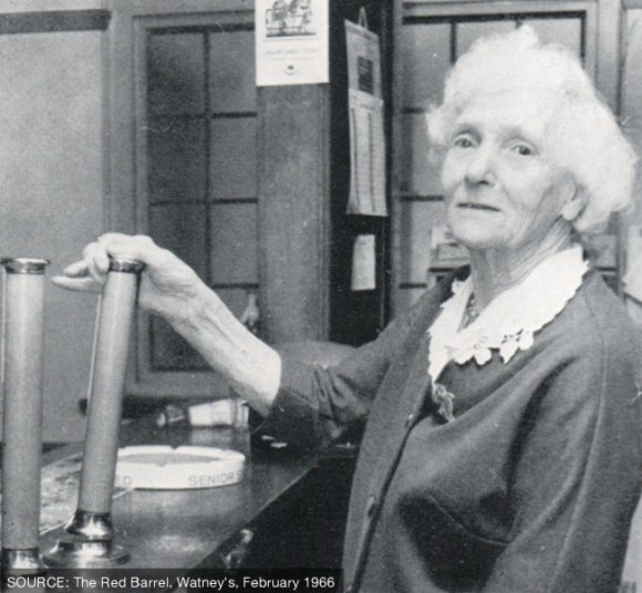 An elderly woman pulling a pint of beer.