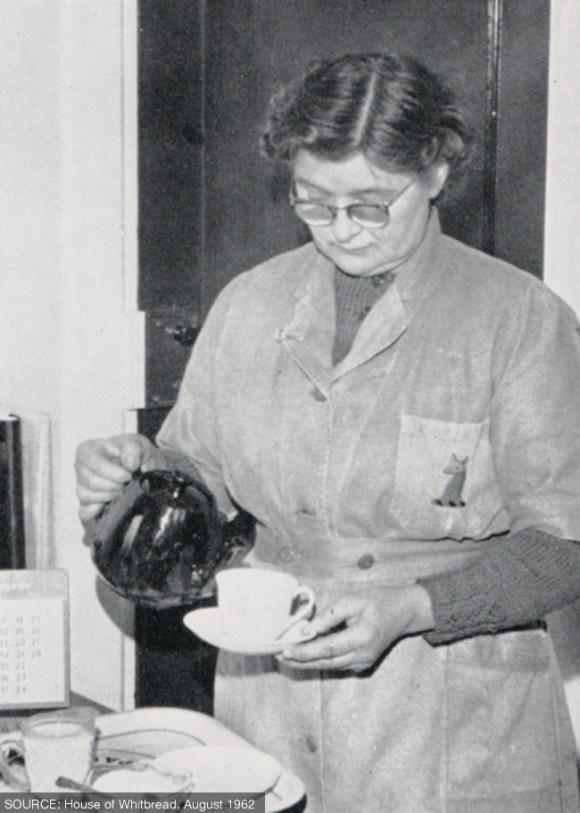 A woman pours a cup of tea.
