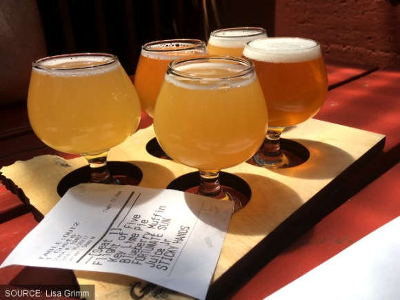 A taster flight of beers with tiny stem glasses and receipt.