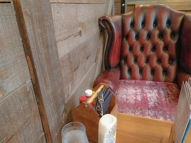 Vintage pub seating and wooden walls.