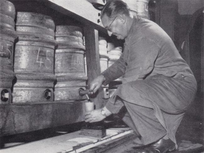 A man dispensing Guinness from a cask.