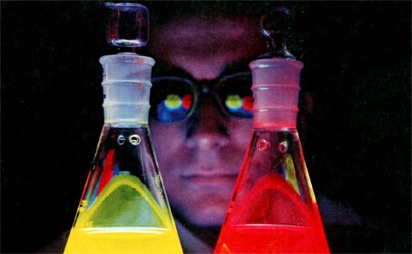 A scientist looks at flasks of colourful liquid.