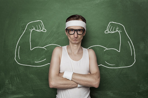 Funny sports nerd flexing fake muscle drawn on the chalkboard