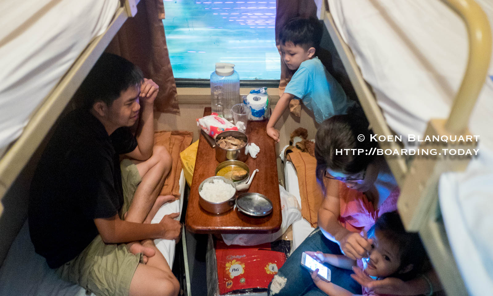 Bin and his family enjoying rice and chicken on the train between Saigon and Hanoi