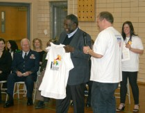 "John Johnson, Rogers Elementary parent and School Board member, presents Ralph Smith with a T-shirt from ""Spread the Words: Read by 3rd"" the grade-level reading initiative in Marshalltown."