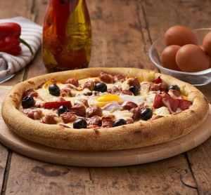 pizza avec des merguez sur une table en bois