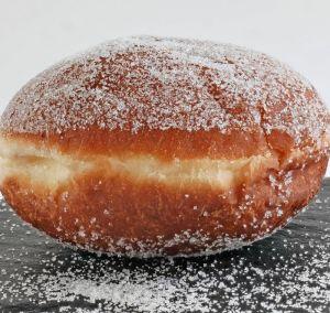 1 un beignet fourré saupoudré de sucre poser sur une assiette en ardoise