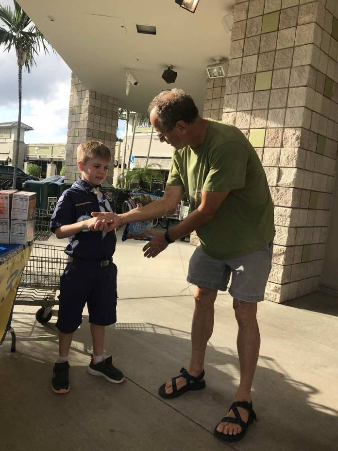 Liam Crawford(8), of Cub Scout Pack 333 in Boca,seals the deal with a hand shake.