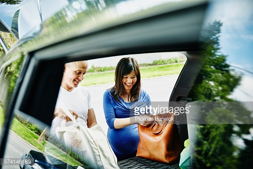 Laughing pregnant couple unpacking trunk of car after shopping