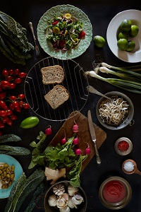 Assortment of fresh ingredients of the vegan cuisine, fresh salad of valerian, sprouts, tomatoes, radishes, spring onions, black tuscan broccoli and limes.
