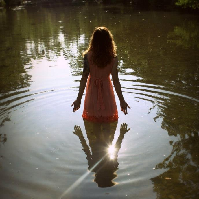 Genevieve from behind, standing thigh deep in a lake. She is wearing a peach colored dress, and her long hair flows down her back. Ripples extend out from her legs in the water, and the sun reflects on the water. She holds her palms out in a gesture of surrender.