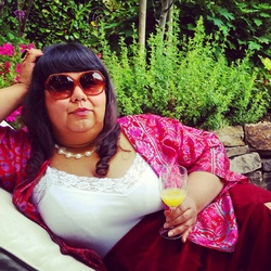 An image of Virgie Tovar. She is brown-skinned, fat, with long dark hair and short bangs. She lounges on a chair in a lush garden, with her head propped up on her elbow. She is wearing large sunglasses, bright pink jacket, burgundy skirt, and pearls. She's holding a champagne glass filled with what looks to be a mimosa. She looks fabulous.