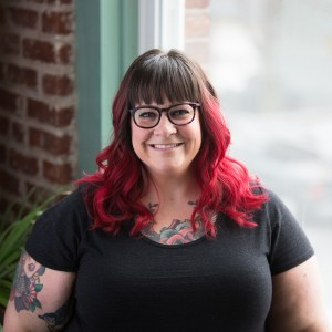 Amber Karnes, creator of Body Positive Yoga. Description: Amber is a white, fat, cisgender woman with dark hair that fades into bright red, glasses, and tattoos. She's smiling at the camera wearing a gray t-shirt. A window and brick wall are behind her. Photo credit: Andrea Killam