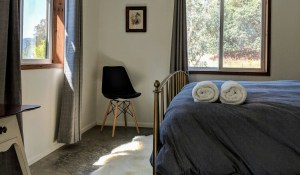 Image description: Bedroom at Sagrada, towels rolled at the end of a bed, chair in the corner, a picture framed on the wall and sun shining through the window
