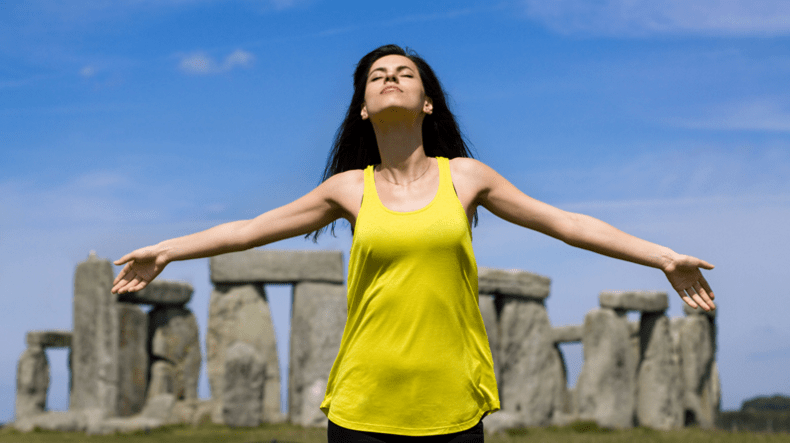 woman with arms outstretched in front of stonehenge