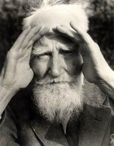 George Bernard Shaw shading his eyes with his hands