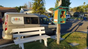 The Little Free Library outside of the Chadwick's home with The Literacy Club's van behind it.