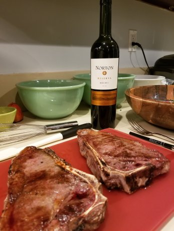 Angle on the kitchen counter with steaks resting in the foreground with wine and salad in the background.