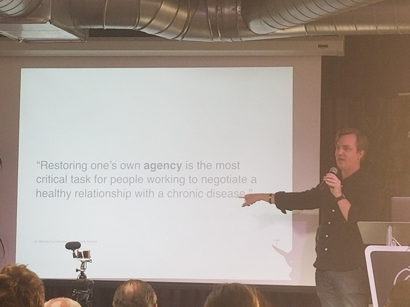 "Matt Lumpkin on stage pointing at a slide on the screen stating ""Restoring one's own agency is the most critical task for people working to negotiate a healthy relationship with a chronic disease."""