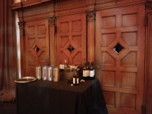 A table with wine service set up in front of the church's wooden paneled confessional area.