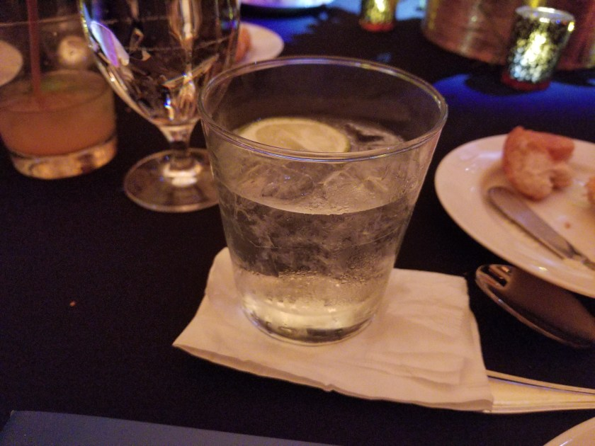 cocktail sitting on a napkin on a table with a black tablecloth