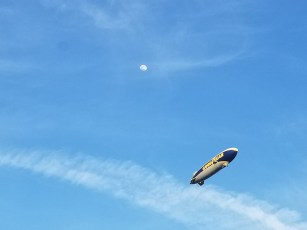 A shot looking up at the blue sky featuring the blimp and an almost full moon.
