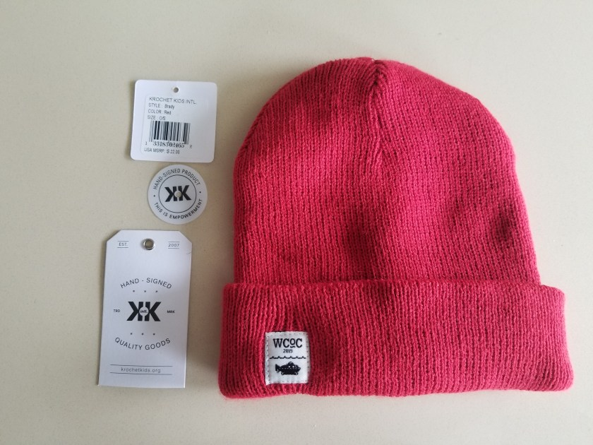 "A red beanie with a tiny square white label with the letters ""WCoC 2019"" over a small line indicating waves over a black submarine shape."