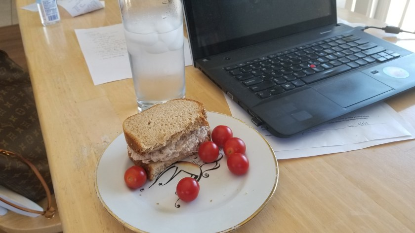 lunch on a plate next to a computer