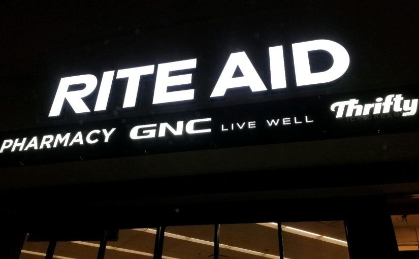 View of black Rite Aid sign light up in the dark